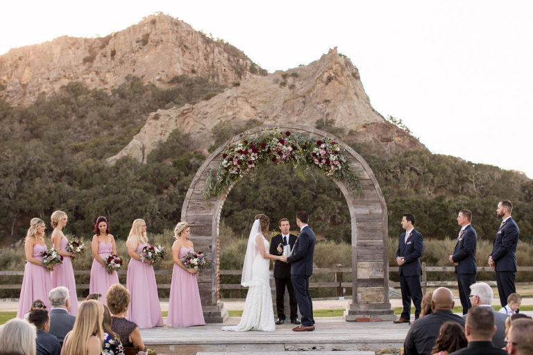 Holland Ranch wedding flowers with burgundy and blush flowers on a rustic arch Flowers by Denise wedding flowers