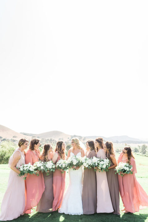 Bridesmaids in dusty rose dusty mauve and pale peach dresses by Show Me Your Mum with white flowers